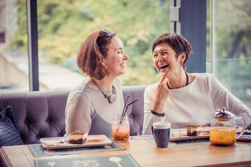 Laughing women enjoying meeting in cafe