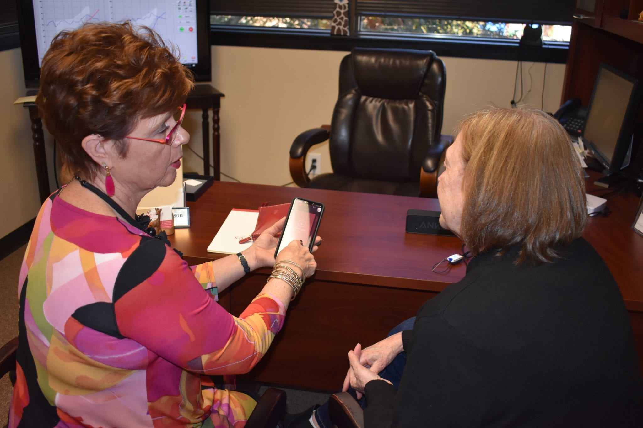 Audiologist showing patient how to use hearing aid app on smartphone
